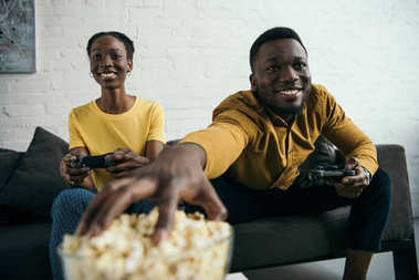 happy young african american couple eating popcorn and playing with joysticks at home
