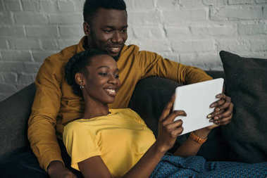 happy young african american couple using digital tablet together at home
