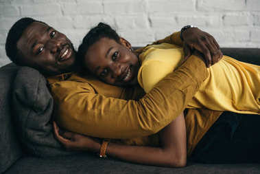 happy young african american couple in yellow shirts lying together on sofa and smiling at camera
