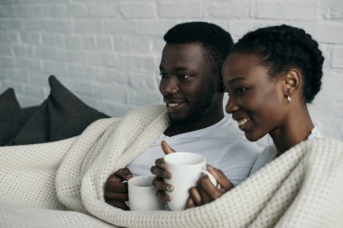 happy young african american couple holding cups of tea and looking away at home