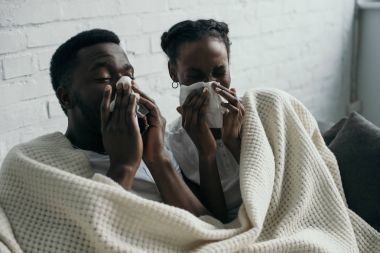 young african american couple holding paper napkins while having flu together at home