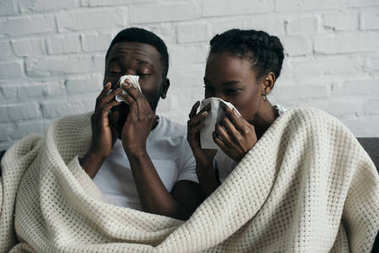 young sick african american couple holding paper napkins and lying under blanket together at home