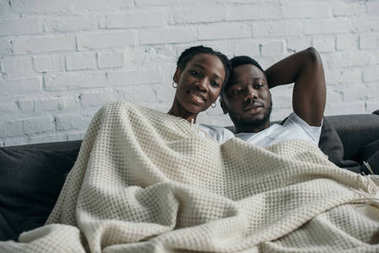 beautiful happy young african american couple lying together under blanket