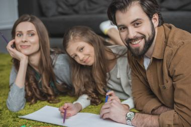 happy parents and daughter drawing with felt-tip pens on floor and looking at camera