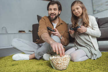 father playing video game with daughter and eating popcorn