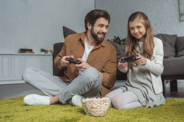 father and daughter sitting on carpet and playing video game
