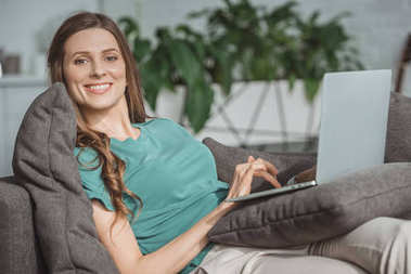 smiling beautiful woman using laptop on sofa at home