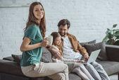 Fényképek apa és lánya néz valamit a laptop és anya gazdaság csésze kávé