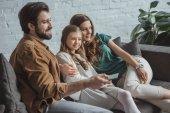 Fényképek boldog szülők és lánya otthon a kanapén tévénézés