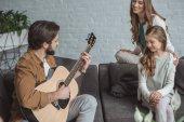 otec hrál na kytaru pro dceru a ženu doma