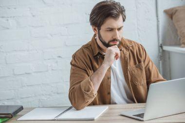 handsome businessman using laptop at workspace