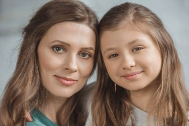 portrait of mother and daughter looking at camera
