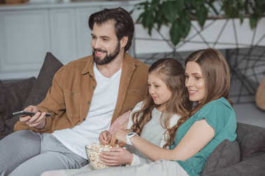 happy parents and daughter watching tv with popcorn at home