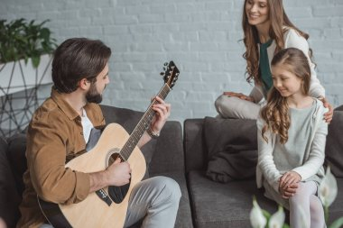 father playing guitar for daughter and wife at home