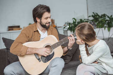 smiling father showing daughter how to play barre chord
