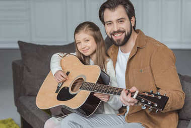smiling father teaching daughter playing acoustic guitar and looking at camera