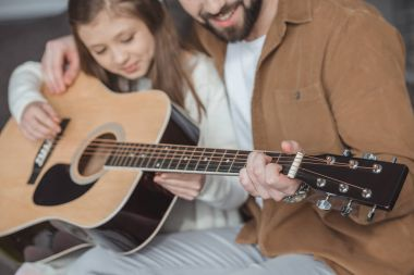 cropped image of father teaching daughter playing acoustic guitar