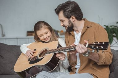 happy father teaching daughter playing acoustic guitar