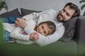 otec a dcera ležela na pohovce a při pohledu na fotoaparát