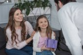 Fotografie daughter presenting gift box to father at home