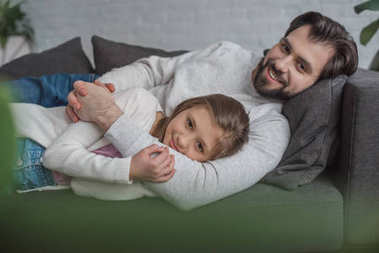 father and daughter lying on sofa and looking at camera