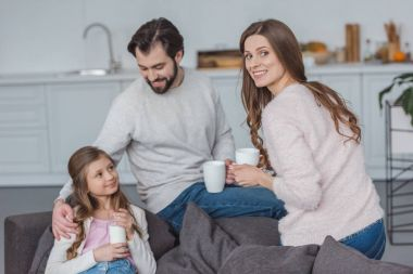 happy parents and daughter with drinks in morning