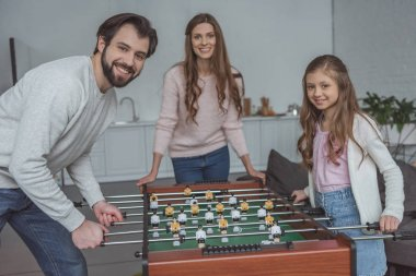 father and daughter playing foosball at home and looking at camera