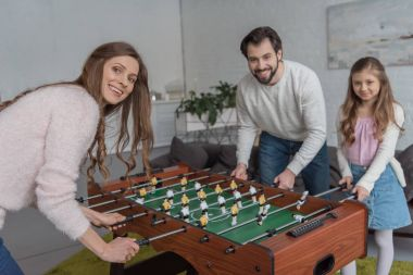 parents and daughter playing table soccer at home