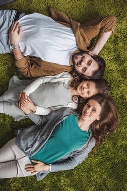 top view of family lying on green carpet and looking at camera