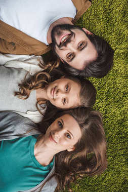 top view of parents and daughter lying on green carpet and looking at camera