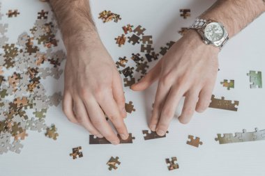 Cropped image of man connecting puzzle pieces at table stock vector