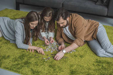 high angle view of parents and daughter connecting puzzle pieces on carpet in living room