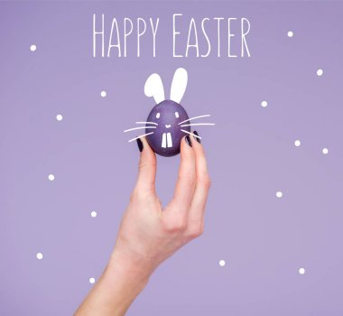 Easter egg in female hand with happy easter lettering