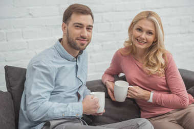 portrait of smiling mother and grown son with cups of hot drinks at home