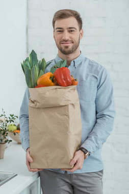 portrait of man with paper bag full of fresh vegetables for dinner in hands at home