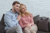 Fotografie portrét usmívající se syna objala matku při odpočinku na pohovce doma