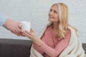 ritagliata attento figlio cresciuto portato tazza di tè alla madre in coperta sul sofà a casa