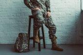 Fotografie částečný pohled vojáka ve vojenské uniformě seděl na židli proti bílé zdi