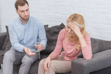careful son giving glass of water and pills to mother with headache on sofa at home