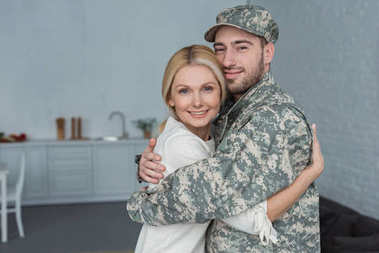Portrait of smiling man in military uniform and mother hugging each other at home stock vector