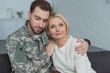 portrait of man in military uniform hugging mother at home