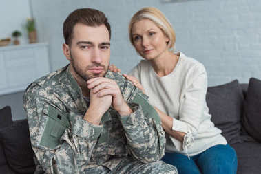 portrait of thoughtful man in military uniform and mother near by on sofa at home