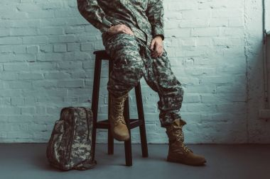 partial view of soldier in military uniform sitting on chair against white brick wall