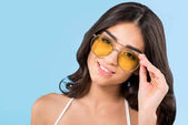 beautiful smiling girl posing yellow sunglasses, isolated on blue