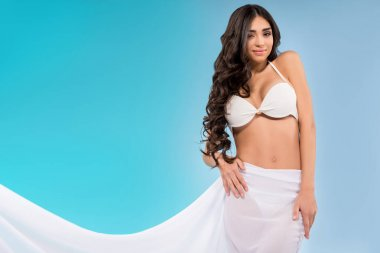 attractive woman in bikini posing with white veil, isolated on blue