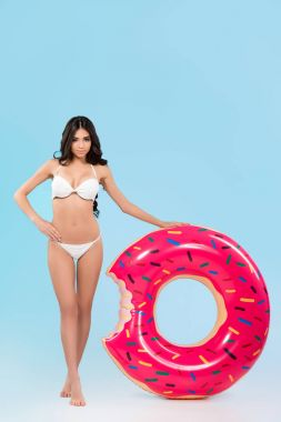 attractive slim girl posing with inflatable donut ring, isolated on blue