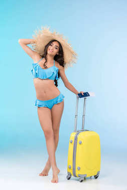 Beautiful slim girl in bikini and straw hat posing with baggage and passport, isolated on blue stock vector