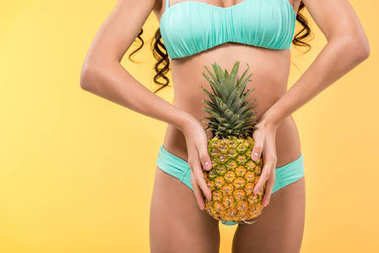 cropped view of tanned girl holding pineapple fruit, isolated on yellow