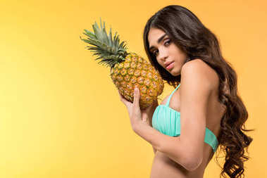 beautiful girl in bikini holding fresh pineapple, isolated on yellow