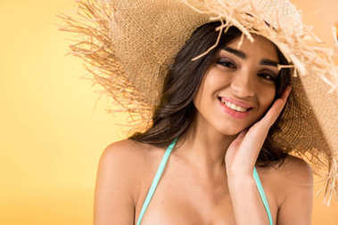 beautiful young woman in straw hat, isolated on yellow